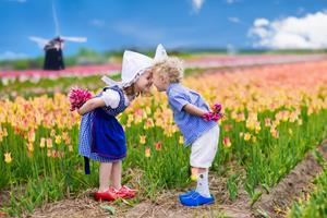 Happy Dutch children playing in blooming tulip flowers field.  Boy and girl wearing traditional national costume, wooden clogs and hat play with tulips next to a windmill in Holland, Netherlands